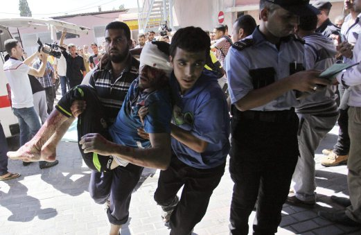 Palestinians carry a man, who medics said was wounded in Israeli air strikes on a house, into a hospital in Khan Younis in the southern Gaza Strip